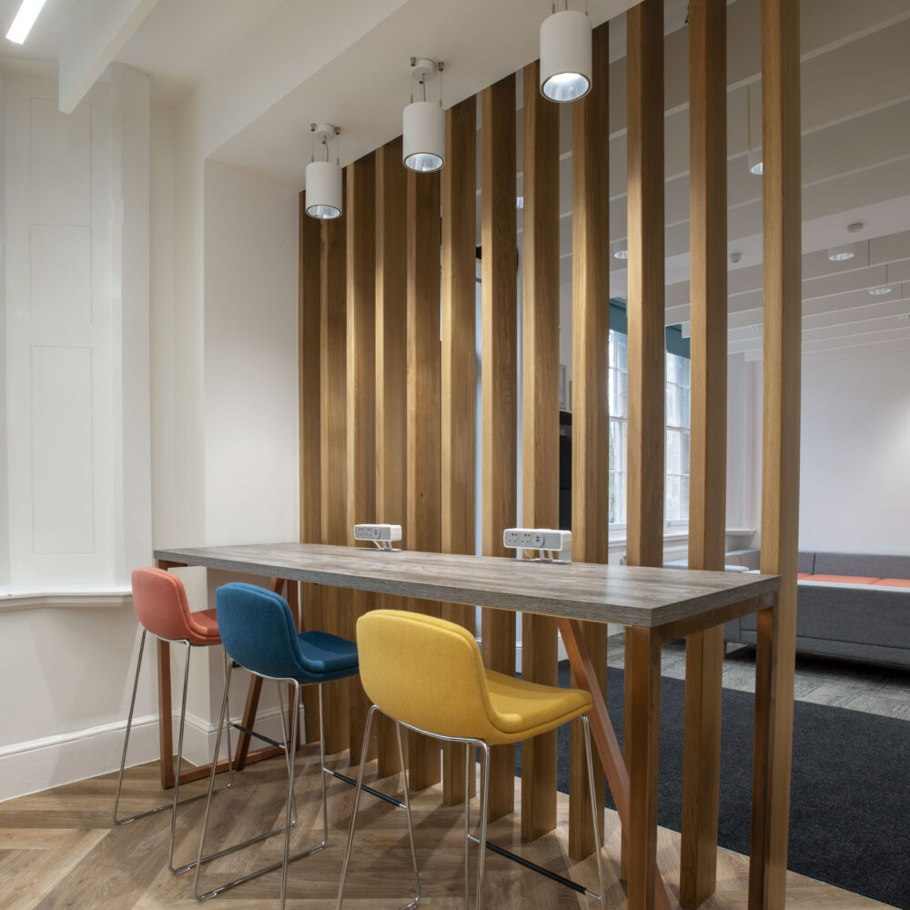 Interior of shared living space, with wooden divider slats, three chairs and a table